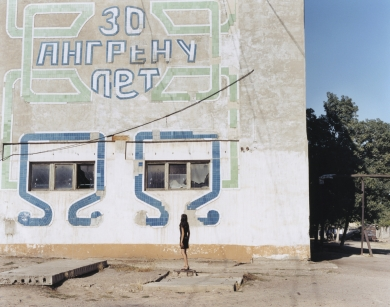 © RIP HOPKINS / AGENCE VUHOME AND AWAYOUZBEKISTAN, 200216/08/02Sveltana Demid in front of an inscription reading : Angren is 30 years old, in the mining town of Angren, 60 kilometres east of Tashkent. She is 21 years old. He is an accountant. Her Russian mother came from Kirgizstan in 1985 and her father's parents came here to build Angren in 1950. She does not know if she will leave.N°10650