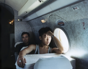 © RIP HOPKINS / AGENCE VU HOME AND AWAY OUZBEKISTAN, 2002  20/08/02 Alexey Khegay and Kulnazar Saribaev in a Yak-40 aeroplane between Tashkent and Nukus. Alexey Khegay is 19 years old. He is a telecommunications student in Tashkent. His Korean grandparents were sent to Nukus in Karakalpakstan from the Russian / Chinese border by Stalin in 1937. He will leave Nukus definitively for Tashkent once he finishes his studies. Kulnazar Saribaev is 47 years old. He is a police captain in charge of Nukus's immigration and visa department (OVIR). His father is Uzbek and his mother is Karakalpak. He wants to leave Nukus for Tashkent. On arrival at Nukus' airport I was arrested and spent a brief spell in prison, I got out by paying a heavy bribe and had to leave the area within 24 hours.  N°10650