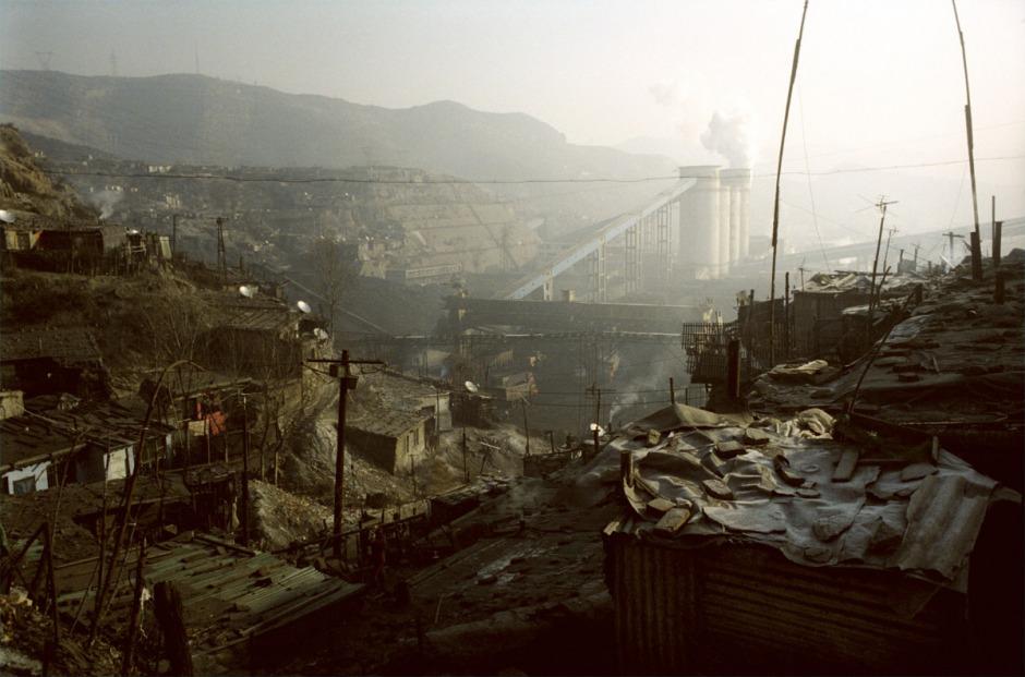 """China, Gujiao, 2006 The coal mine in Gujiao. The mingongs, the worker - farmers coming from the poor region of China go down the mine for 150 euros per month. Not enought to build a real house around the """"hole"""". Without any social protection, without security inside the mine, they are the most exposed to the risk. The pollution of the factories is also a breathing disease factor. Xiu Yu Jun says : """"before we were respected as miners, now we are the last on the social rank.""""  China, Gujiao, 2006 Gujiao, ville minière. Le salaire des ouvriers migrants ne leur permet pas de se construire une vraie maison au bord du """"trou"""". Dans les bidonvilles à l'air charbonneux, sans eau courante et sans protection sociale, les maladies respiratoires prolifèrent et les maisons s'effondrent une à une, fragilisées par les galeries rongeant la montagne de l'intérieur.  """"Du temps de Mao, en tant que mineur, nous étions des héros, mais aujourd'hui, nous ne sommes plus rien"""". Xiu Yu Jun, mineur.  Samuel Bollendorff / Agence VU"""