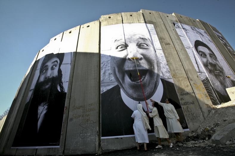 """West Bank, Bethlehem, 4 March 200728 Millimetres, Face 2 Face.Pasting on the Separation wall. Security fence, Palestinian side.""""Holy Triptich"""": Reb Eliyahu, Brother Jack and Cheikh Aziz.Cisjordanie, Bethléem, 4 mars 200728 Millimetres, Face 2 Face.Installation sur le mur de séparation. Barrière de sécurité, côté palestinien.""""Triptyque sacré"""": Rabbin Eliyahu, Frère Jack et Cheikh Aziz.JR"""