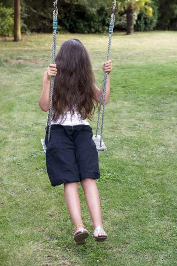 France, 31 August 2009 - What would be a faceless world ? Little girl on a swing.