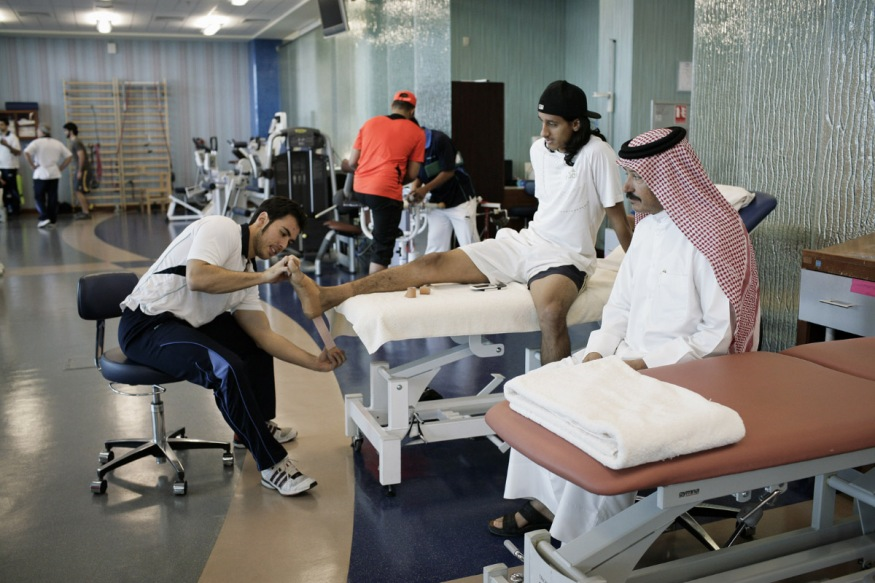 Qatar, Doha, 19 April 2012 - Physiotherapy room of Aspetar Sport private clinic.Al Shamal soccer player with his father.