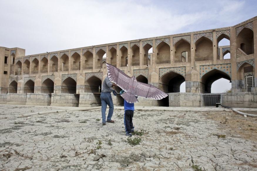 Iran, Isfahan, 13 November 2013 - Pol e Khadju - Khadju Bridge and the empty river zayanderoud. Playing with a kite.